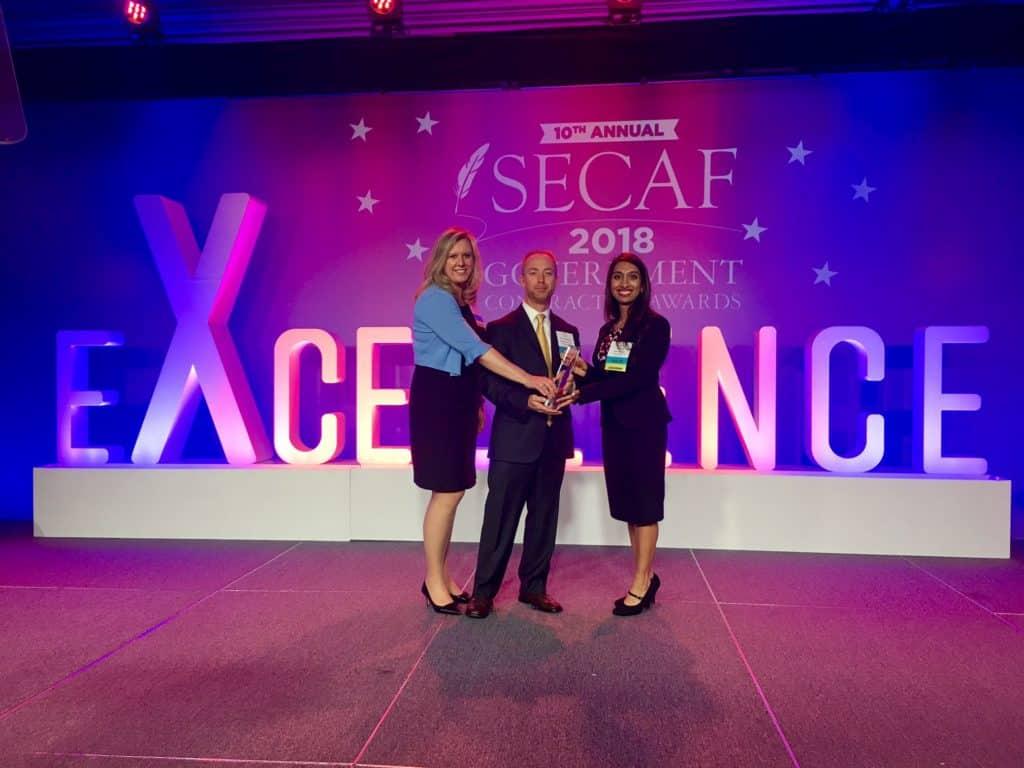 IntegrityM Partners Cheryl Gordon, Chris Coleman, and Nisha Shajahan accept the 2018 SECAF Government Contractor Award